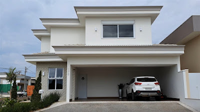 A garagem da casa fica na rua frontal do lote, possui 7,05 metros de largura e duas portas: a da esquerda é um acesso secundário para as salas e a da direita conduz para o corredor externo de serviços, ligado à lavanderia.