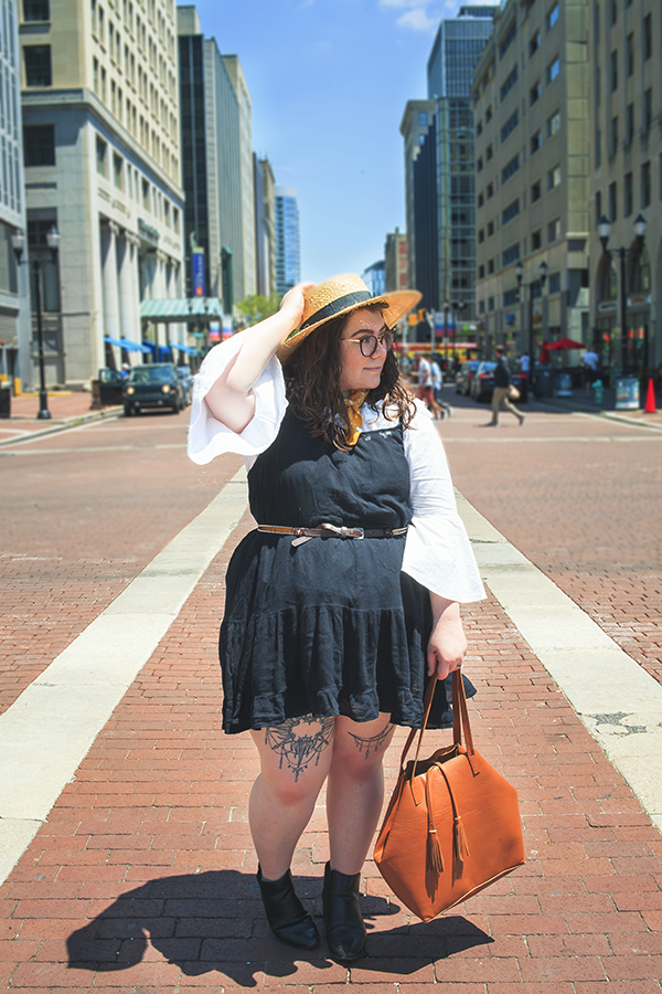 An outfit consisting of a straw boater hat, a white off the shoulder ruffle neck hem blouse, black tiered camisole dress, and black heeled chelsea boots.