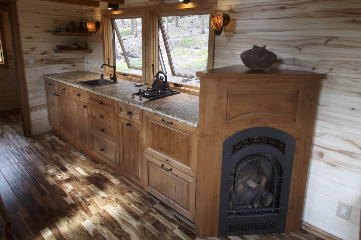 07-Kitchen-and-Fireplace-Simblissity-Tiny-House-Stone-Cottage-on-Wheels-www-designstack-co