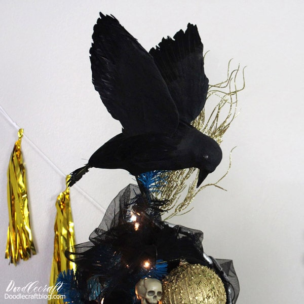 Make a haunted display in your home with a bright blue Christmas tree decorated with spooky skulls, pumpkins, chains and topped with black crows for the perfect Halloween tree.