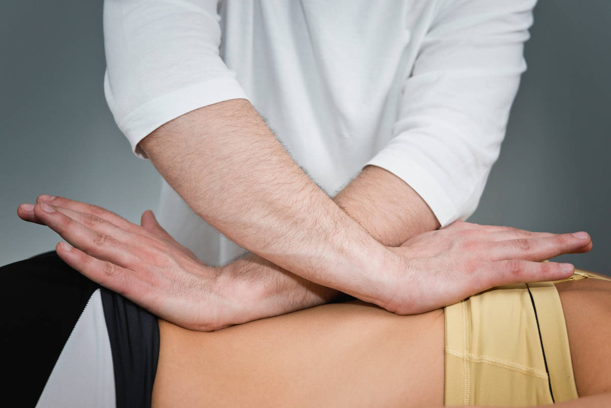 A male massage therapist performing a cross-shear technique on a client.