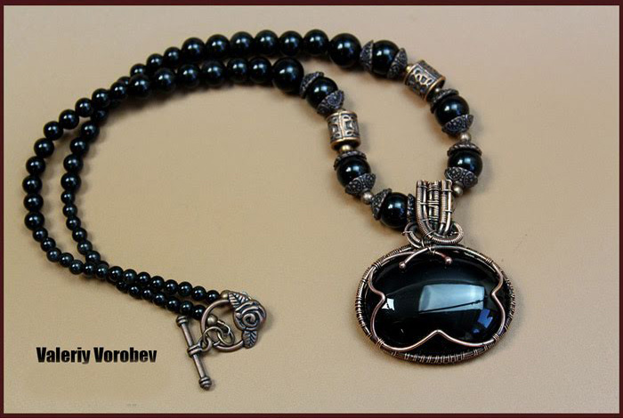 Pendant handmade from copper wire with cabochon from natural stone black onyx.