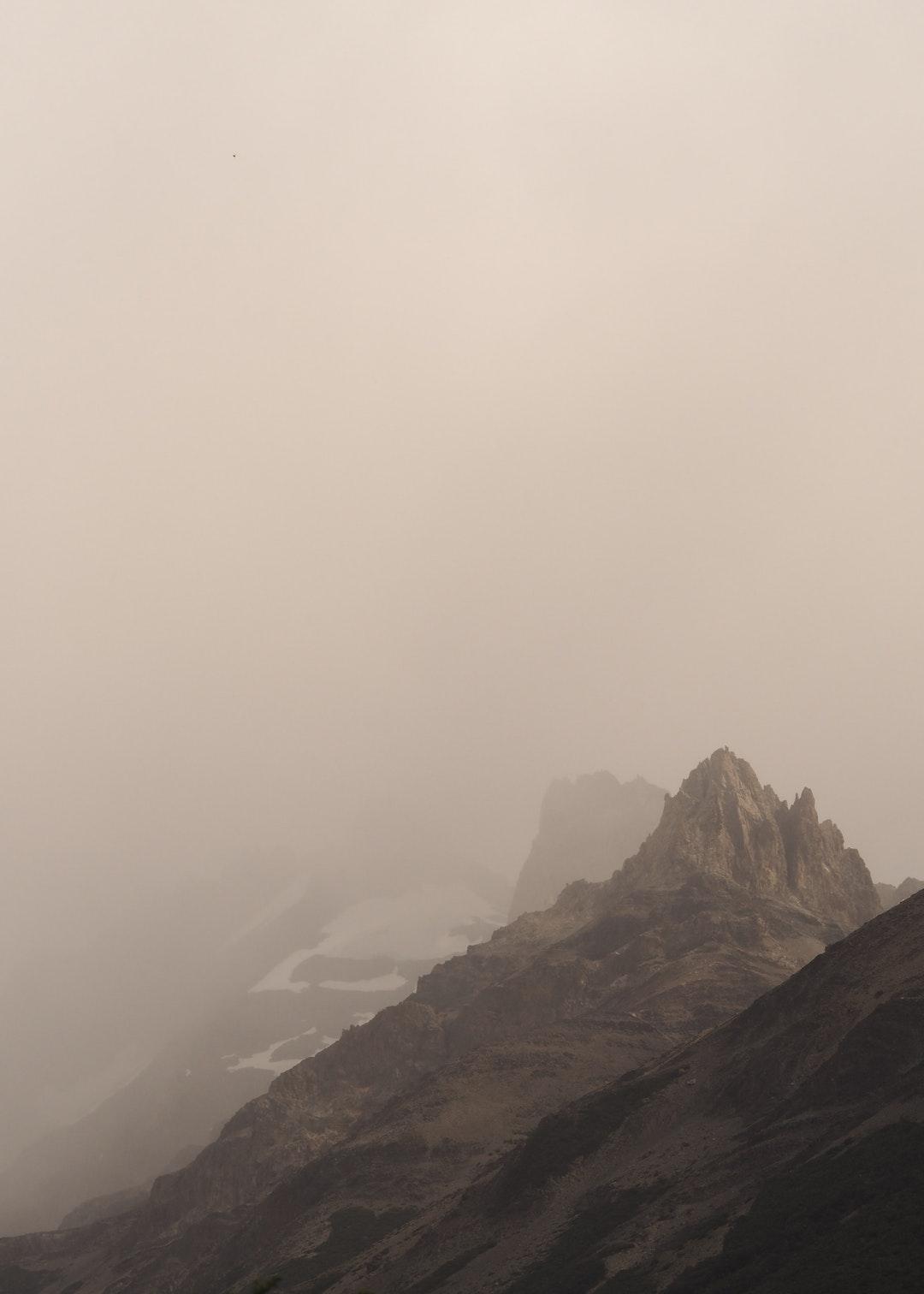 جبل منخفض مع خلفية بنية و ضباب كثيف - خلفيات ايفون X