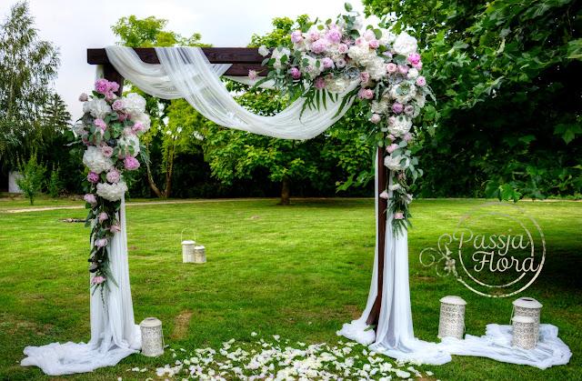Pergola ozdobiona kwiatami na plenerowym ślubie.