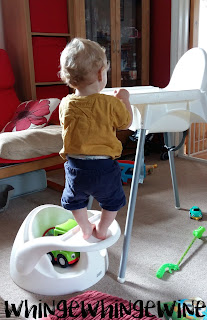 The small one standing on a baby seat