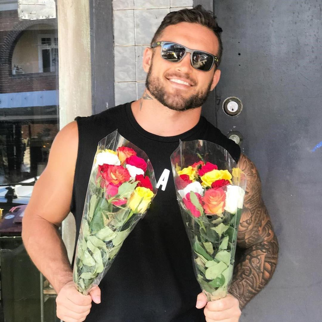 sexy-man-smiling-flowers-wishing-happy-valentines-day