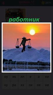 мужчина работник с ведрами на рассвете несет два ведра соли