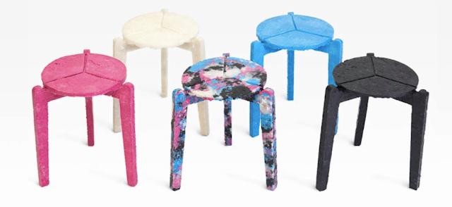 A foto mostra cinco cadeiras sem encosto, também se parece com banquinhos, cada uma possui três pés, o fundo da foto é branco. Da esquerda para a direita: uma cadeira completamente rosa escuro pink, outra cadeira toda branca - um branco fosco, a outra é colorida de azul, rosa, preto e branco - as cores estão todas misturadas, como se tivesse sido jogada, a outra cadeira é toda da cor azul - um azul claro e a última cadeira é completamente preta.