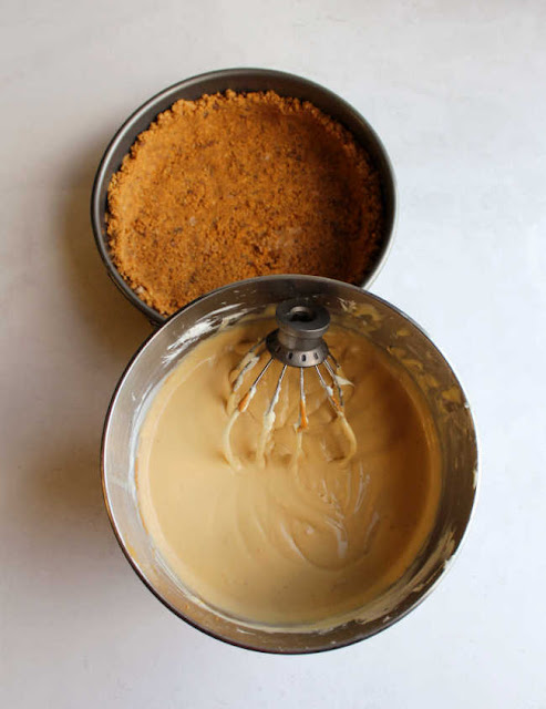 mixer bowl of peanut butter cheesecake filling in front of peanut butter cookie crumb and toffee crust