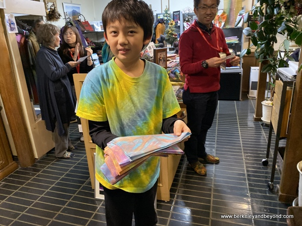 young boy delivers finished student projects at AlpenRose cafe at Geocolor:  Hachimantai Geothermal Dyeing in Hachimantai city, Japan