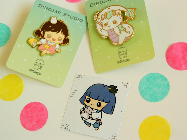 A photo showing enamel pins of two Studio Ghibli characters: Dragon Haku and Mei, plus a sticker of Haku. They are surrounded by colourful polkadots