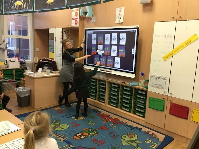 Opettaja ja vuorossa oleva oppilas pelaavat muistipeliä Smart-taululla luokan edessä.