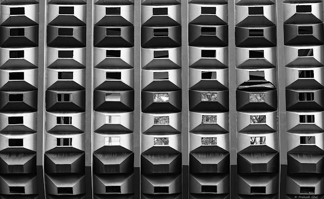 A Black and White Minimal Art Photograph of the Facade of a building, with Rectangles in Repetition as a Pattern