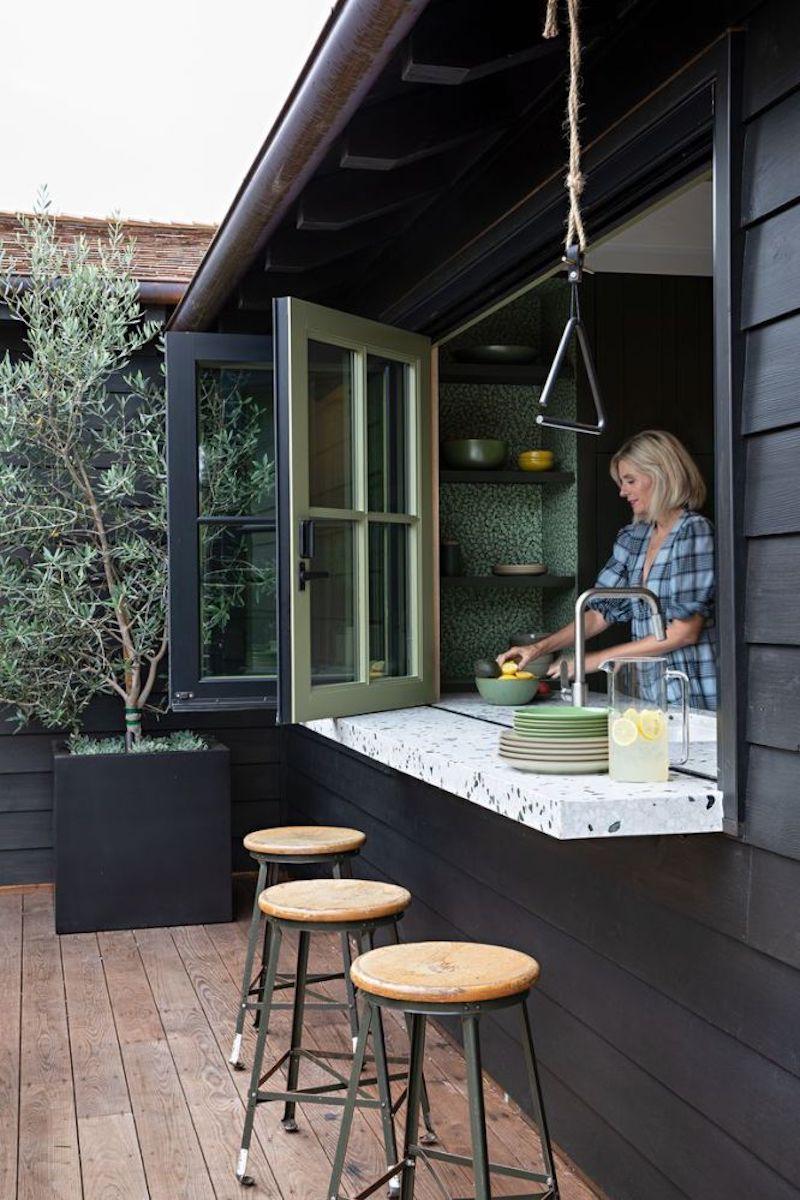 Ventanas que sirven de pasaplatos y a la vez barra alta con taburetes en el porche.