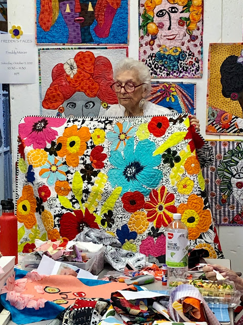 Freddy holds one of her floral collage quilts at New Pieces Quilt Shop, Berkeley CA