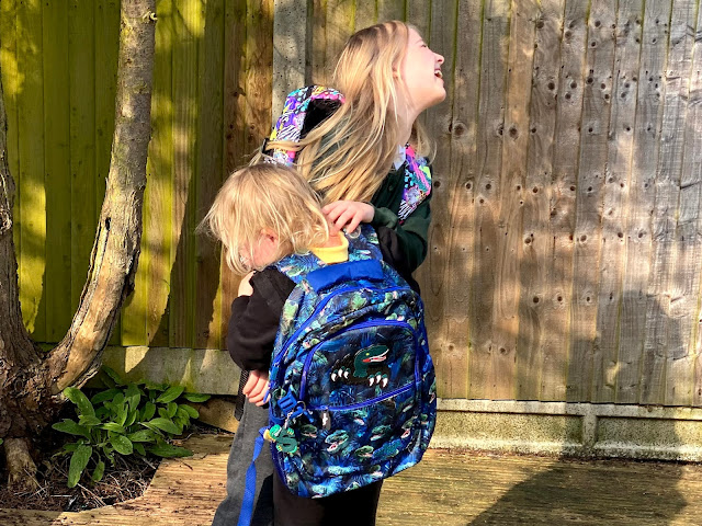 Siblings in school uniform and Smiggle review backpacks playfighting