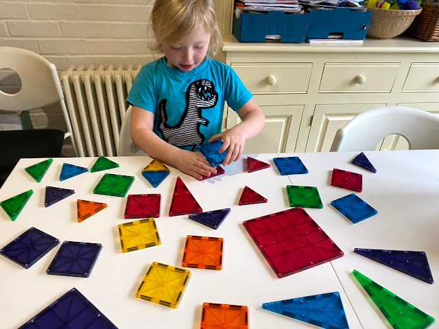 clear colour pieces of magna-tiles laid out on a table in front of a preschooler.