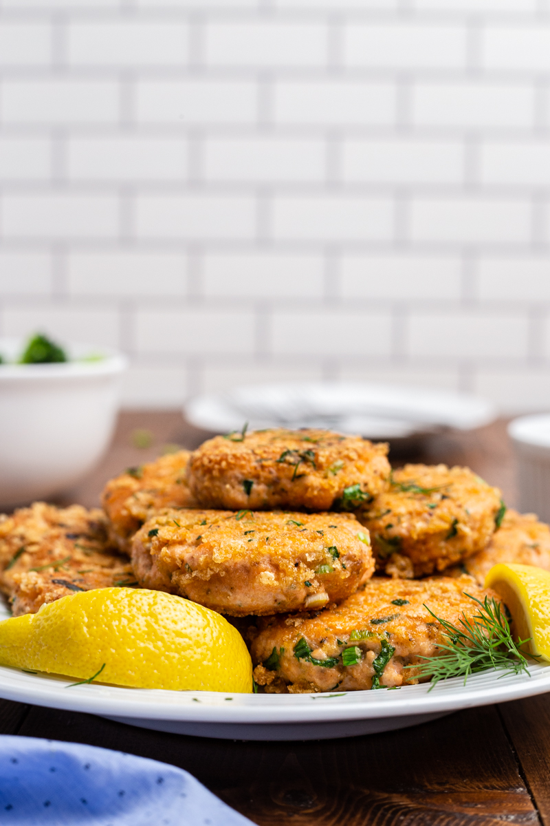 Side view photo of Keto Salmon Cakes (Salmon Patties) on a white plate on a wooden table.