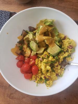 a bowl with tofu scramble, avocado, potatoes, cherry tomatoes, and sauce