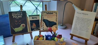 Na sztalugach trzy książki o motylach oraz napis Dzień motyla. Pod sztalugami motyle i kwiaty w wiklinowym koszyku