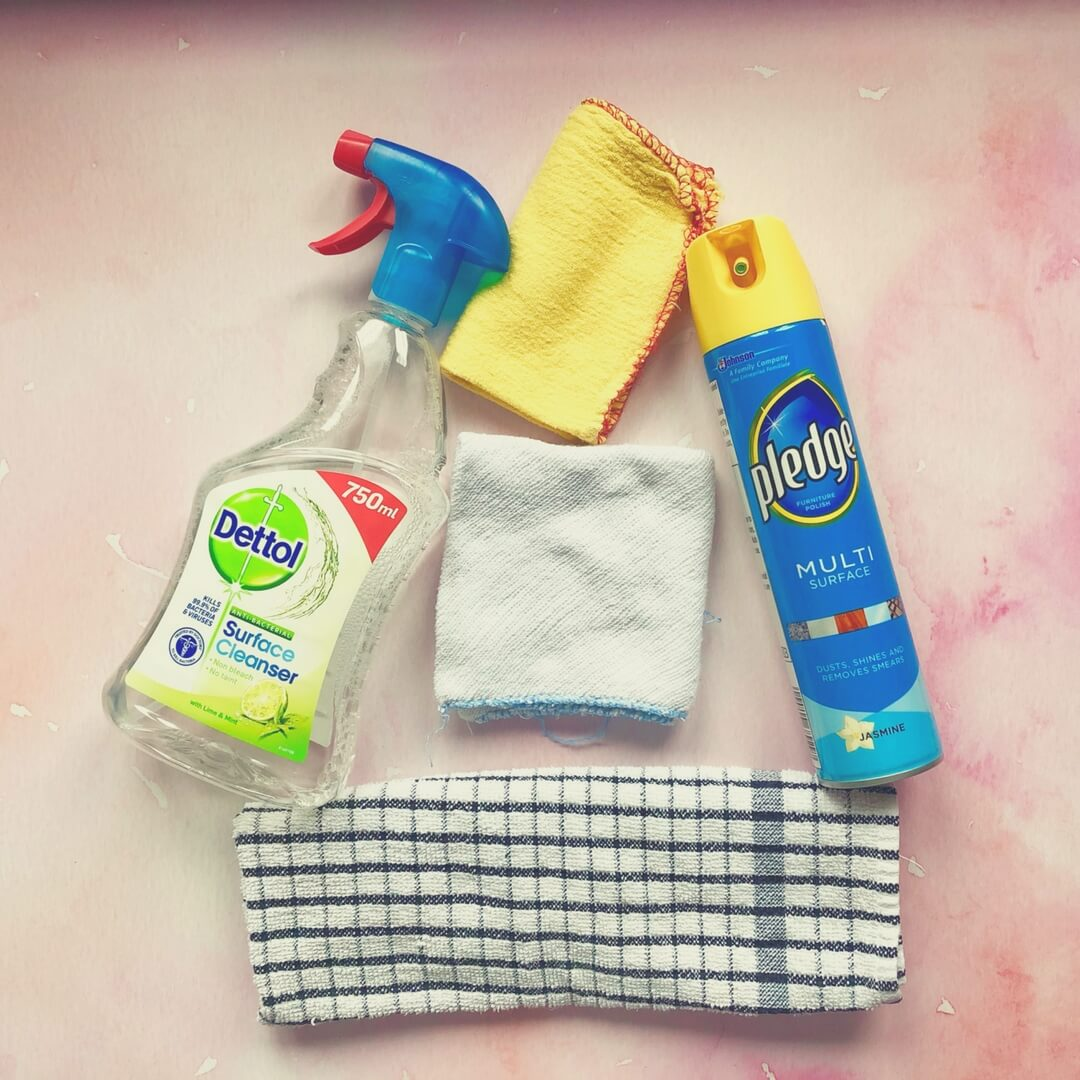 A bottle of Dettol and a can of Pledge polish sit on a pink background, in between them is an orange duster, a white dishcloth and a blue checked tea-towel.