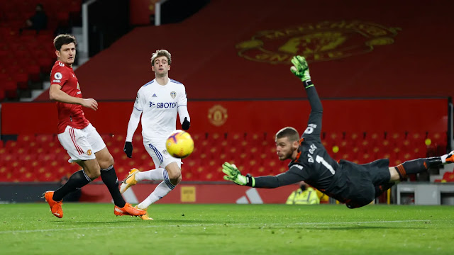 Manchester United players Harry Maguire and David De Gea watch Patrick Bamford strike