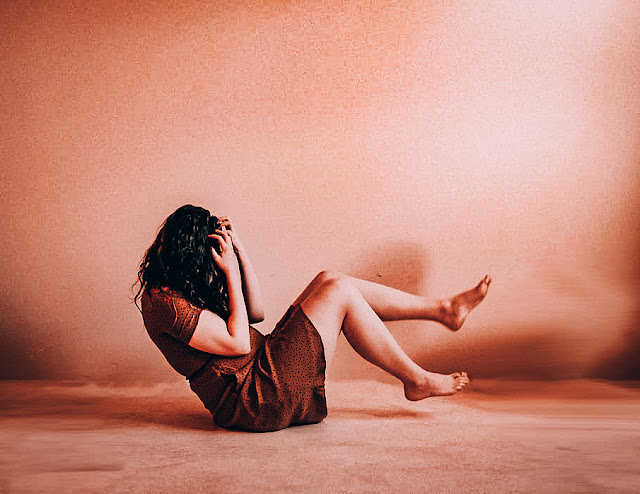 Image of a woman in a brown dress sitting on the floor. She is screaming and holding her head, upset and angry. The image depicts mental health.