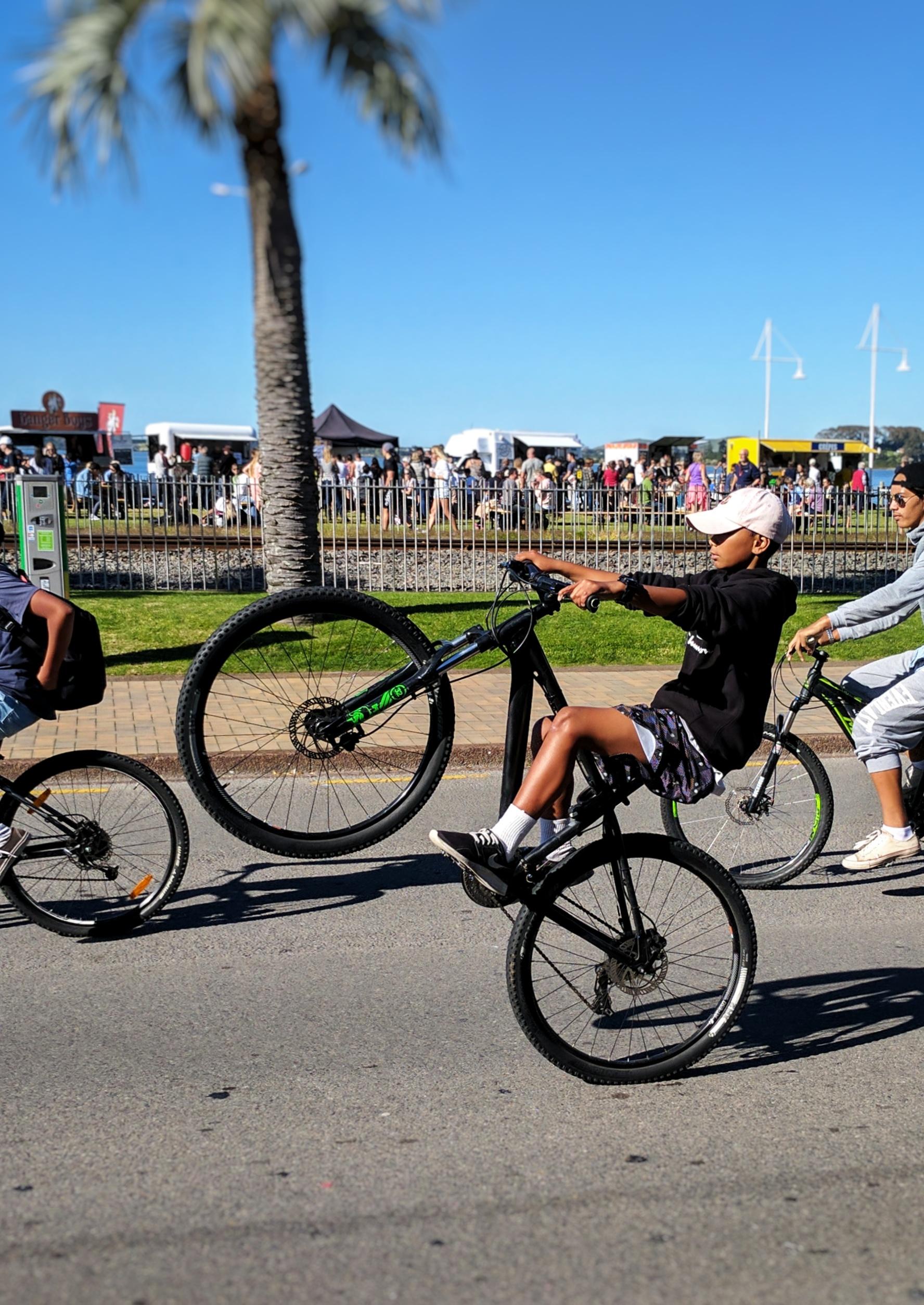 Kid doing a wheelie on the Tauranga waterfront