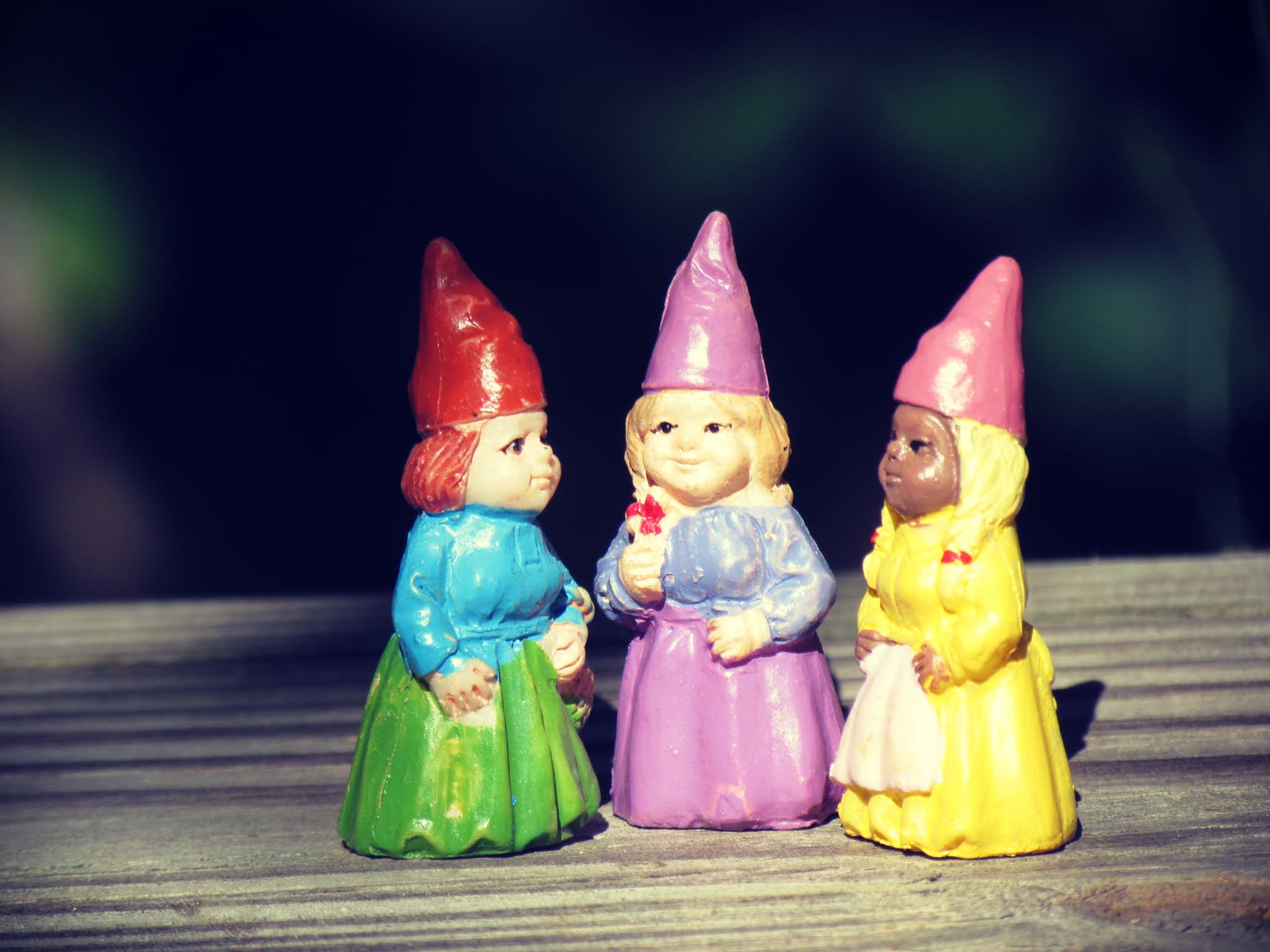 Three of cups tarot card with three gnome sisters celebrating the seasons of life with a green witch coven of sisterhood