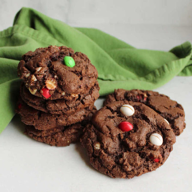 stack of chocolate cookies dotted with red, white and green m&m candies