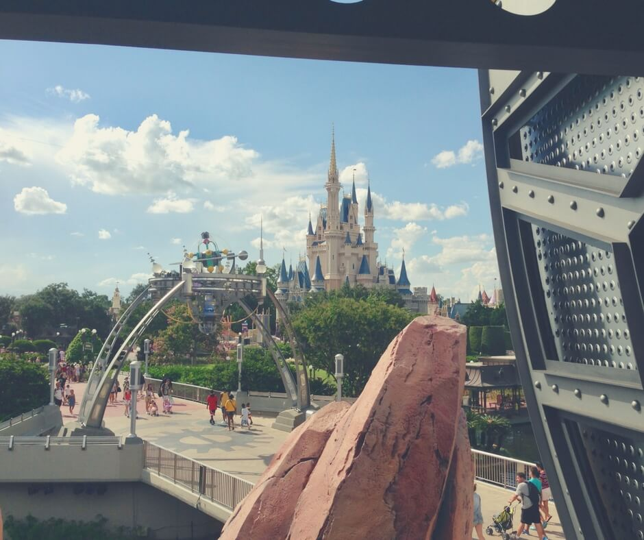 "A photo taken from the Transit Authority Peoplemover at Magic Kingdom. Cinderella's Castle stands just to the right, sun shining down on it's spires. The tomorrowland entrance, with spinning planets atop a metal mobile is in the centre of the photo. Trees and flowers block the view of the bottom of the castle. People walk into and out of tomorrowland. A large orange rock stands close to the camera blocking some view. Image for ""How to get a much-needed rest at Magic Kingdom""."