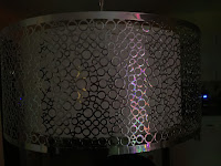Hanging metal lamp shade with circle reflecting colored lights.