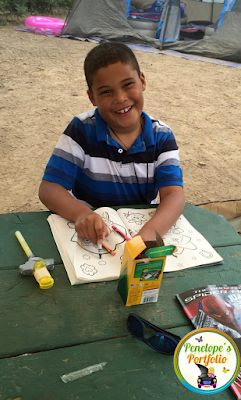 A boy coloring while camping