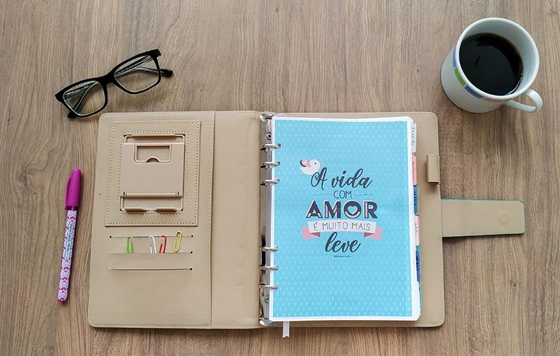 """A imagem mostra uma agenda no centro, aberta na primeira página, em que é possível visualizar a capa do planner, de fundo azul turquesa, com os dizeres em preto """"a vida com amor é muito mais leve"""". Ao lado do planner, compondo a imagem, estão uma caneta rosa, um óculos preto e uma xícara de café"""