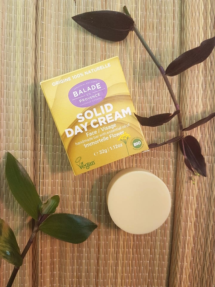 Balade en Provence plastic free solid face cream with the circular bar underneath the cardboard packaging and all surrounded by plants
