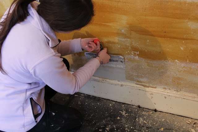 using a taping knife to fill walls