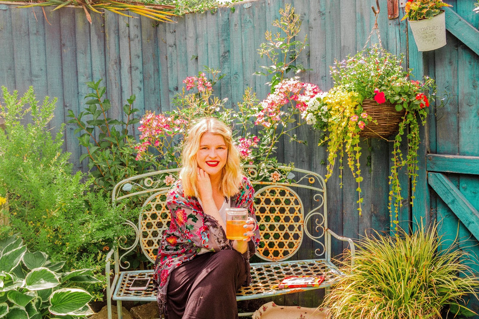 blonde girl in garden reading and drinking tea