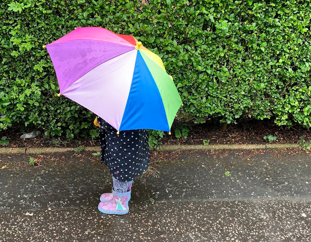 A toddler under a rainbow umbrella on a pavement next to a bush