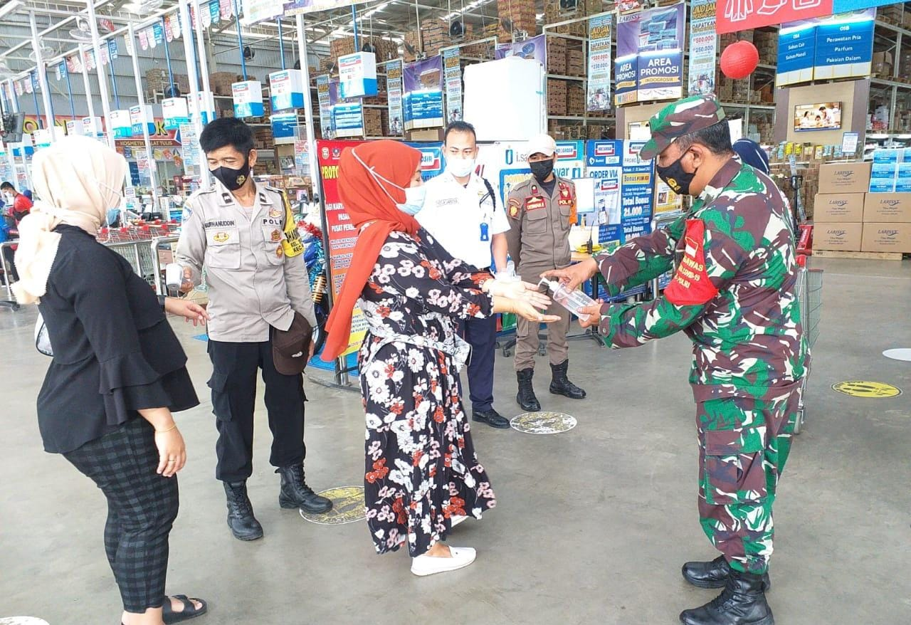 Babinsa Koramil 410-06Kedaton Kodim 0410KBL Pelda Romulo, bersama sejumlah personel Satuan Tugas Penanganan Covid-19, melakukan upaya pencegahan penyebaran virus Covid-19 di pusat perbelanjaan Indogrosir