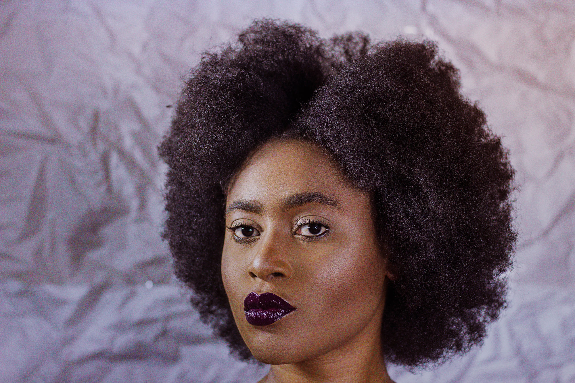 Beauty editorial African woman with afro purple glossy lips