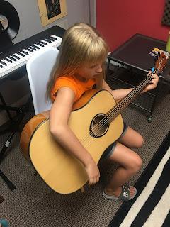 Girl plays guitar.