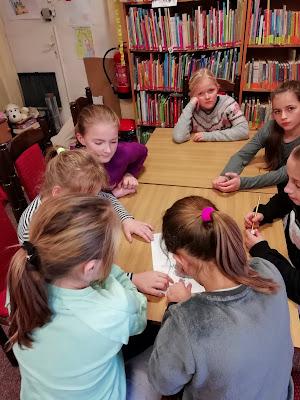 Dzieci rozwiązują zadania związane z Kubusiem Puchatkiem