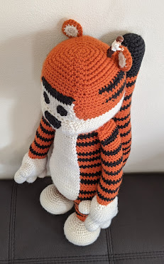 A crochet Hobbes (tiger) plushie standing up, with photo from above. A lego man is standing next to the ear, which is about the same size. This is to show the scale of the toy as it's very large.