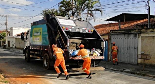 A imagem mostra uma rua residencial, um caminhão de lixo e os catadores de lixo colocando os resíduos dentro do caminhão. Os trabalhadores vestem um uniforme laranja.