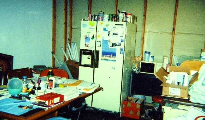 A room with a table and a large refrigerator. It is extremely cluttered, with papers, books, bottles, boxes and so on every surface and stacked in corners