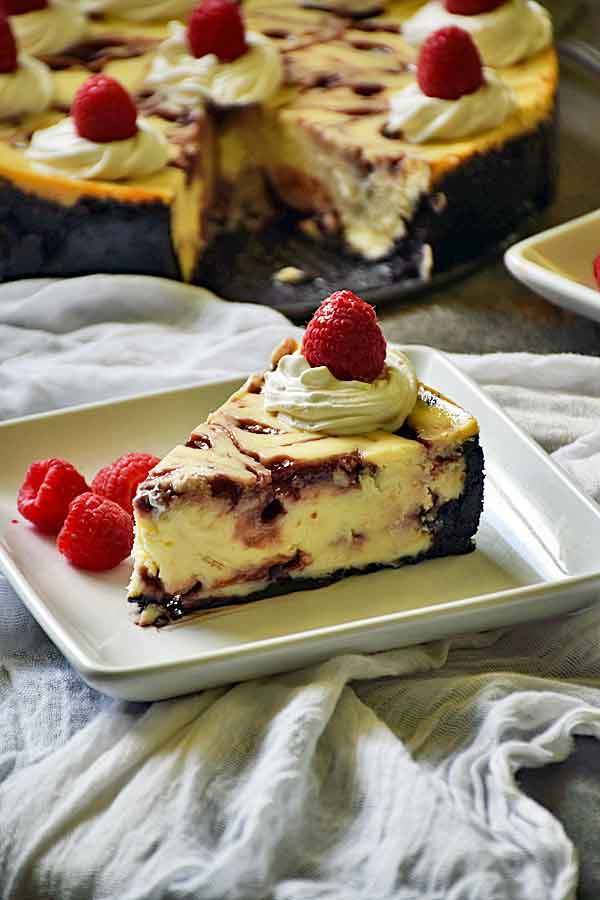 Slice of Raspberry White Chocolate Cheesecake on a white plate with fresh raspberries