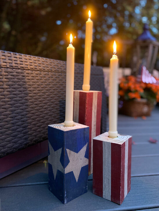 Candle holders painted in red, white, and blue with lit candles