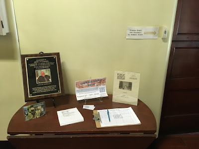 Small wooden desk with some fliers, a clipboard, and a plaque with text and a man's photo.