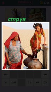 женщина и девочка набирают воду из колонки на улице, струя прямо в кувшин