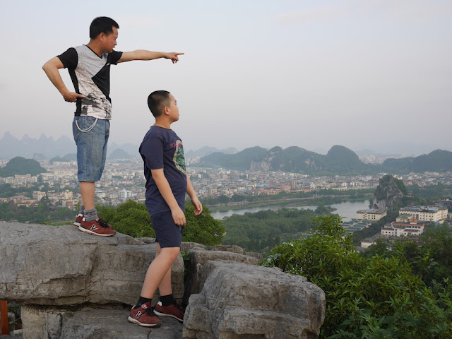 boy looking towards where a man is pointing while standing at the top of Crane Peak at Diecai HIll